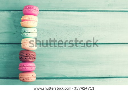 Colorful macrons over turquoise wood - stock photo