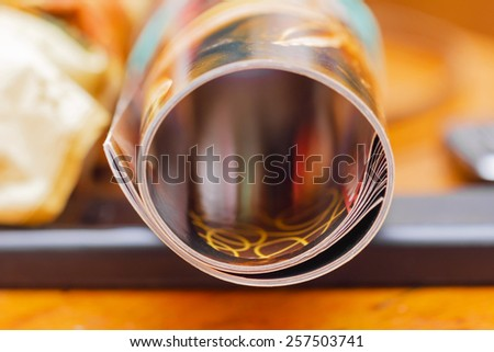 Colorful magazine rolled in tube in light boke - stock photo