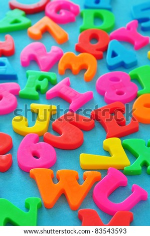 Colorful magnetic letters and numbers on blue background