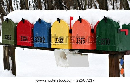 Colorful mailboxes covered in snow - stock photo