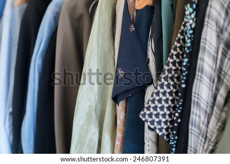 Colorful male and female clothes hanging - stock photo