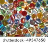 Colorful marbles in a glass bowl on top of a light table. - stock photo