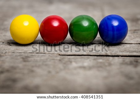 colorful marbles in a line on a wooden table - stock photo