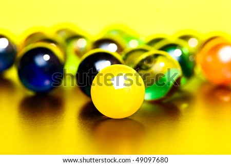 Colorful marbles on yellow background - stock photo