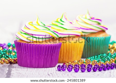 Colorful Mardi Gras cupcakes with beads, shallow depth of field