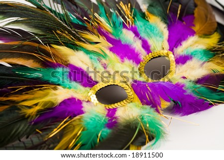 Colorful mardis gras mask closeup in green gold and purple slightly out of focus on edges - stock photo