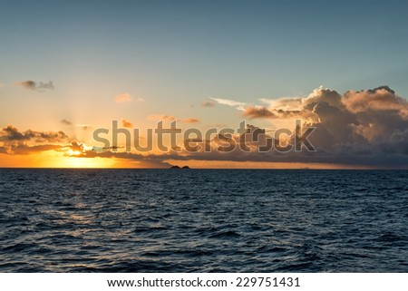 Colorful marine sunset over a tropical ocean with the fiery orange sun dipping down towards the horizon with low lying cumulus cloud formations in a twilight sky - stock photo