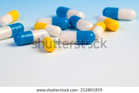 Colorful medical capsules on white background. - stock photo