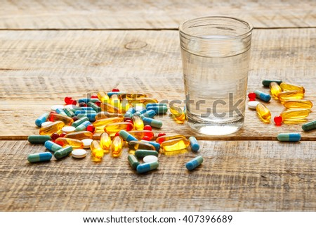 colorful medical pills with water on wodden table - stock photo
