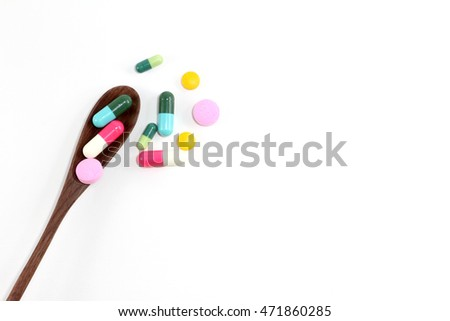 colorful medicine on the wooden brown spoon on the white background