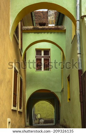 Colorful medieval architecture house with arcades and passage in the fortified citadel of Sighisoara, Romania, a UNESCO World Heritage Site. - stock photo