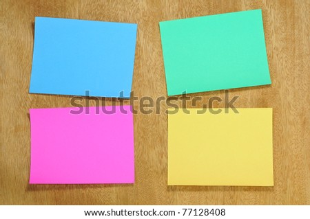 Colorful memo notes on plywood board background