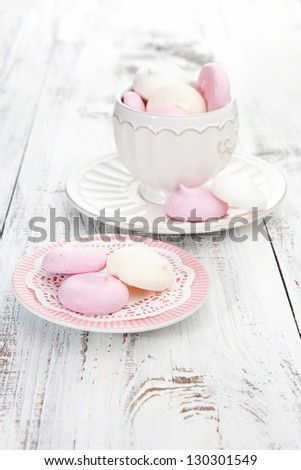 Colorful meringues on a white wooden table