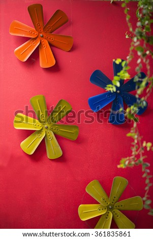 Colorful metal flowers decoration on red wall.  - stock photo