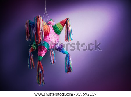"Colorful mexican ""piñata"" or pinata used in birthdays on a purple background - stock photo"