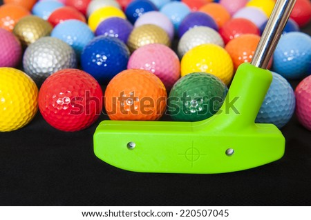 Colorful mini golf balls with a green club - stock photo