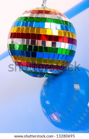 Colorful mirror-ball with reflection over blue - stock photo
