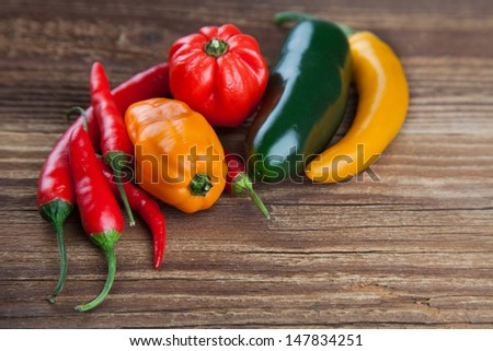 Colorful mix of fresh chili lying on old wood in a rural style