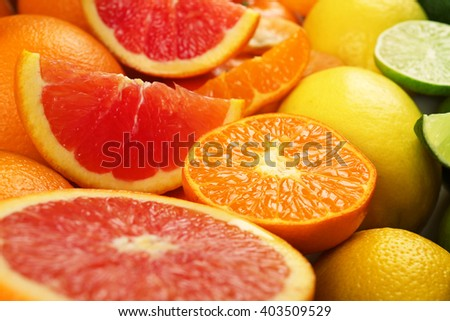 Colorful mixed citrus fruit sorted and lined up in rows with slices and halves, close up - stock photo
