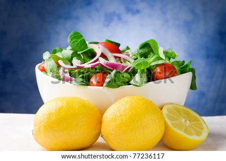 Colorful mixed salad inside a bowl on white towel in front of blue background