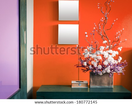 Colorful modern interior wall decorate with artificial flowers in ceramic vase - stock photo