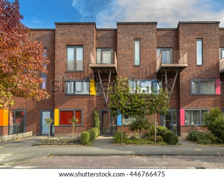 Colorful modern suburban family rowhouses in a lively proper neighborhood with trees and gardens