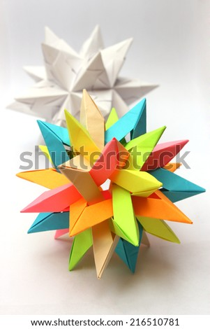 Colorful modular origami paper star with white star in the background - stock photo