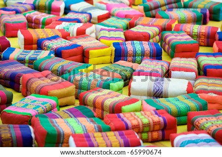 Colorful monk's prayer or meditation cushions scattered in the courtyard of Wat Pho temple in Bangkok - stock photo
