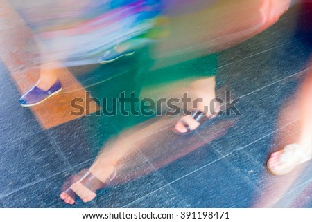Colorful motion blur people walking on the tile floor - stock photo