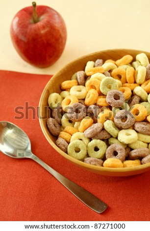 colorful muesli in wooden bowl and red apple on table