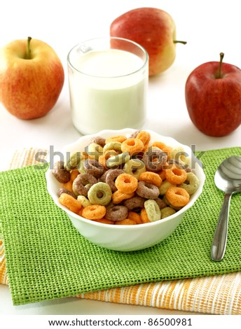colorful muesli in wooden bowl, glass of milk and apples