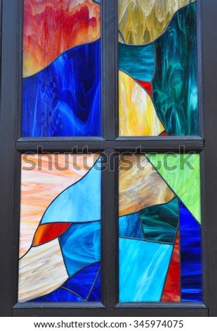 Colorful  multicolored stained glass window with irregular block pattern in a hue of blue, square format - stock photo