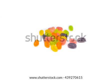 Colorful Multiple jelly bean candy sweets spilled over the white surface as a background composition - stock photo