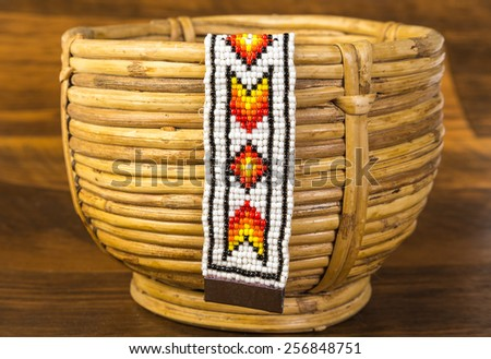 Colorful Native American beaded bracelet hanging from vintage spiral woven wicker basket against rustic wood background. - stock photo