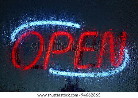 Colorful neon open sign seen through a rainy night - stock photo