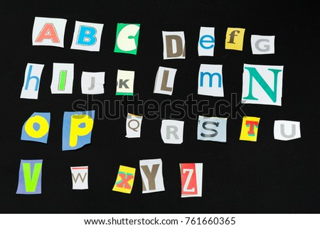 Colorful newspaper alphabet isolated on black