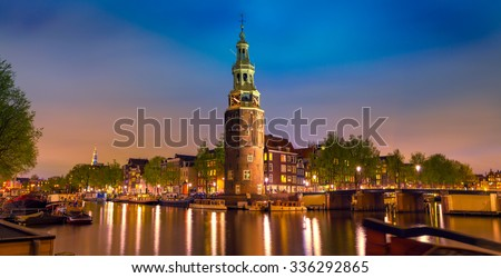 Colorful night scene with Montelbaanstoren tower on bank of the canal Oudeschans in Amsterdam, Netherlands. - stock photo