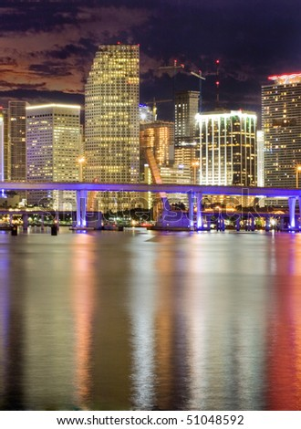Colorful night view of city of Miami Florida with downtown buildings and bridge