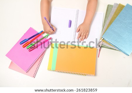 Colorful Notebooks, and pens on white background withh hand - stock photo