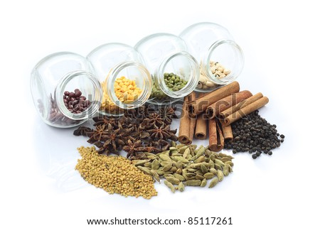 Colorful nuts in transparent glass storage and herbs. Isolated white background. - stock photo