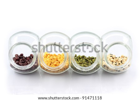 Colorful nuts in transparent glass storage. Isolated white background. - stock photo