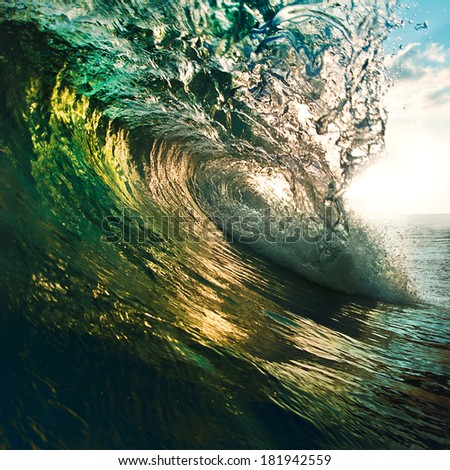 Colorful ocean wave breaking at sunset. - stock photo