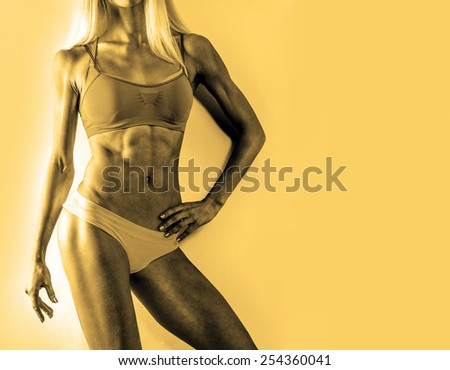 Colorful of blonde bodybuilder young adult sexy girl with long hair Portrait of slim sporty cut VERY HOT woman standing against gray TEXTURED WALL Copy space for inscription flat stomach with press - stock photo