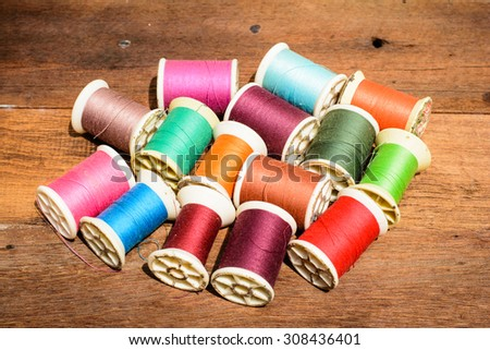 Colorful of thread on reel put on wooden desk