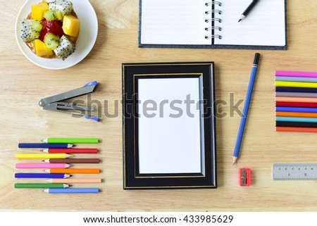 Colorful Office and study art stationery objects on wood table with open notebook and Blank photo frames - stock photo