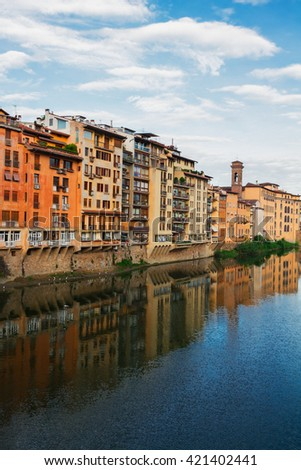 colorful old town houses reflecting in river Arno waters at summer day, Florence, Italy