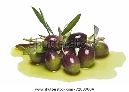 Colorful olives with leaves covered on olive oil and isolated over a white background. - stock photo