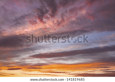 Colorful orange and yellow clouds at sunset. - stock photo