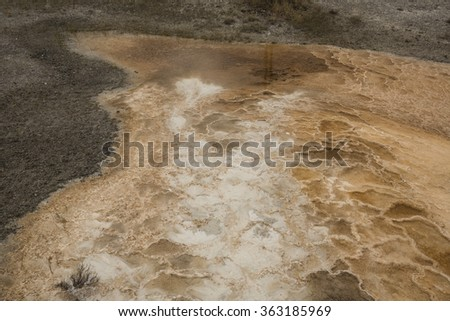 Colorful, orange geothermal streams and pools of hot water with white carbonate deposits and ridges, overlying the travertine rock of Mammoth Hot Springs in Yellowstone National Park, Wyoming. - stock photo