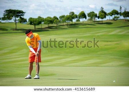 Colorful orange golfer puttng and focus on his golf ball on green - stock photo